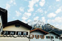 MITTENWALD, GERMANY - DECEMBER 2018: roofs of old houses with snowcapped mountain on the background. MITTENWALD, GERMANY - DECEMBER 2018: roofs of old houses royalty free stock photography