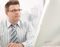 Mittler-Erwachsener Geschäftsmann, der Bildschirm betrachtet stockbild