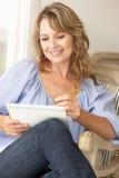 Mittlere Altersfrau, die auf Anmerkungsauflage skizziert Lizenzfreie Stockfotografie
