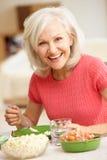 Mittlere Altersfrau, die Mahlzeit isst Stockfotografie