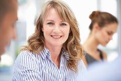 Mittlere Altersgeschäftsfrau in der Sitzung stockfotografie
