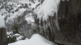 Mittlere Ansicht von Eiszapfen des Eises mit fallendem Schnee stock footage
