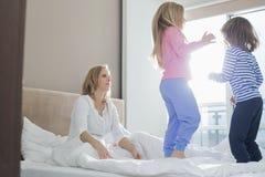 Mittlere erwachsene Eltern, die spielerische Kinder im Schlafzimmer betrachten Lizenzfreie Stockfotografie