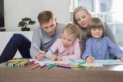 Mittlere erwachsene Eltern mit den Kindern, die zusammen zu Hause zeichnen Lizenzfreie Stockfotos