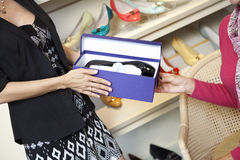 Mittlere erwachsene Frau, die dem reifen Kunden im Schuhgeschäft Schuhe gibt Stockbilder
