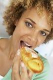 Mittlere erwachsene Frau, die ein Gebäck isst Stockbild