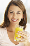 Mittlere erwachsene Frau, die ein Glas Orangensaft anhält Lizenzfreies Stockbild