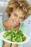 Mittlere erwachsene Frau, die eine Platte des Brokkolis anhält lizenzfreie stockfotos