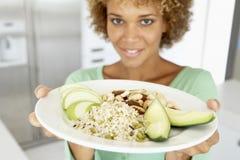 Mittlere erwachsene Frau, die eine Platte mit gesunder Nahrung anhält Stockfotos