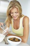 Mittlere erwachsene Frau, die gesundes Frühstück isst Lizenzfreie Stockfotos