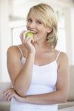 Mittlere erwachsene Frau, die grünen Apple isst Stockbild