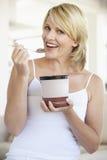 Mittlere erwachsene Frau, die Schokoladen-Eiscreme isst Stockbilder