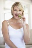 Mittlere erwachsene Frau, die Sellerie-Steuerknüppel isst lizenzfreie stockfotografie