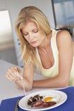 Mittlere erwachsene Frau, die ungesundes Frühstück isst Lizenzfreies Stockfoto