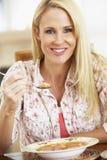 Mittlere erwachsene Frau, welche die Suppe, lächelnd an der Kamera isst Stockfotos