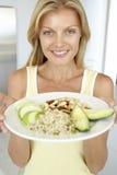 Mittlere erwachsene Frauen-Holding-Platte mit gesunden Nahrungsmitteln Stockfotos