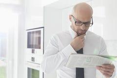 Mittlere erwachsene Geschäftsmannlesezeitung zu Hause Lizenzfreie Stockfotos