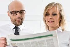 Mittlere erwachsene Geschäftspaar-Lesezeitung in der Küche Lizenzfreie Stockfotografie