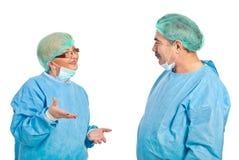 Mittlere gealterte Chirurgen, die Gespräch haben Stockbilder