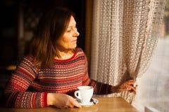 Mittlere gealterte Dame in der gestreiften Strickjacke, die während des Fensters mit einem Tasse Kaffee schaut lizenzfreie stockbilder