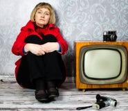 Mittlere gealterte Dame, die auf altem Fußboden sitzt Lizenzfreies Stockbild
