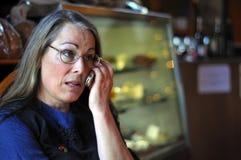 Mittlere gealterte Frau, die auf Handy spricht Lizenzfreies Stockbild