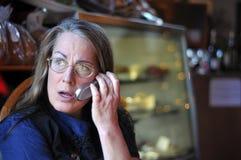 Mittlere gealterte Frau, die auf Handy spricht Lizenzfreie Stockfotos