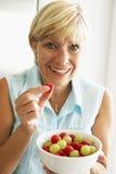 Mittlere gealterte Frau, die eine Schüssel Frucht isst Lizenzfreie Stockfotografie