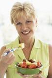 Mittlere gealterte Frau, die frischen Fruchtsalat isst Lizenzfreie Stockfotografie
