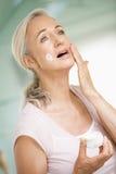 Mittlere gealterte Frau, die Gesichtssahne aufträgt Stockbilder
