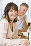 Mittlere gealterte Frau, die mit anderen Kursteilnehmern studiert Lizenzfreies Stockbild