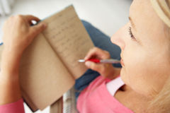 Mittlere gealterte Frauen, die in Notizbuch schreiben Stockfotografie