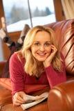 Mittlere gealterte Frauen-Lesezeitschrift, die auf Sofa liegt Lizenzfreies Stockfoto