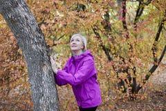 Mittlere gealterte kaukasische Frau steht allein nahe zum Baum am Herbstpark Hände auf dem Baum, helle Freizeitkleidung, weißes d lizenzfreie stockfotografie