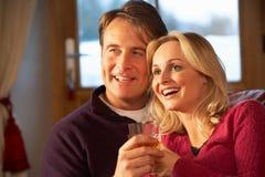 Mittlere gealterte Paare auf Sofa mit Whisky Stockfotos