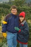 Mittlere gealterte Paare betriebsbereit, Weihnachtsbaum zu schneiden lizenzfreies stockfoto