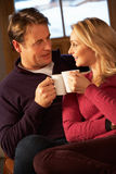 Mittlere gealterte Paare, die auf Sofa mit heißen Getränken sitzen Lizenzfreies Stockfoto