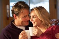 Mittlere gealterte Paare, die auf Sofa mit heißen Getränken sitzen Lizenzfreie Stockfotografie