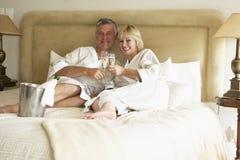 Mittlere gealterte Paare, die Champagne im Schlafzimmer genießen Stockfotos