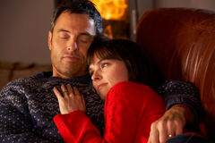 Mittlere gealterte Paare, die durch Cosy Protokoll-Feuer streicheln Lizenzfreie Stockfotografie