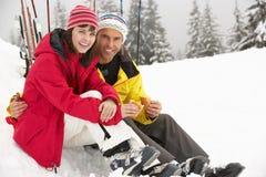 Mittlere gealterte Paare, die Sandwich am Ski-Feiertag essen lizenzfreie stockfotografie