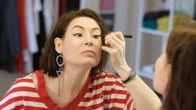 Mittlere gealterte Schönheit, die den Spiegel beim Handeln des Makes-up betrachtet stock video footage