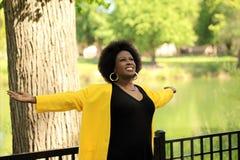 Mittlere gealterte schwarze Frau mit den Armen ausgestreckt Stockfotos