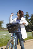 Mittlere gealterte gesunde Frau mit Wasserflasche auf Mountainbike Stockbild