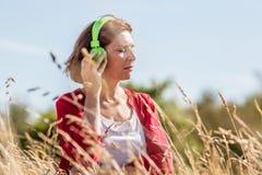 Mittlere Greisin, die draußen Ruhe mit Musik genießt Stockbild