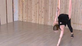 Mittlere Greisin, die gymnastische Übung in der Hängematte im modernen Studio tut stock footage