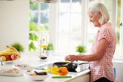 Mittlere Greisin, die Mahlzeit in der Küche kocht Stockfoto