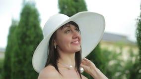 Mittlere Greisin in einem Kleid und weißen in einem Sonnenhut ist, betrachtend lächelnd und den Himmel und genießt den sonnigen T stock video footage