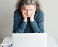 Mittlere Greisin frustriert mit Computer lizenzfreie stockbilder