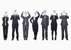 Mittlere Gruppe Geschäftsleute in Folge, die Papier mit Fragezeichen, undeutlich gemachtes Gesicht, Atelieraufnahme halten Lizenzfreies Stockbild
